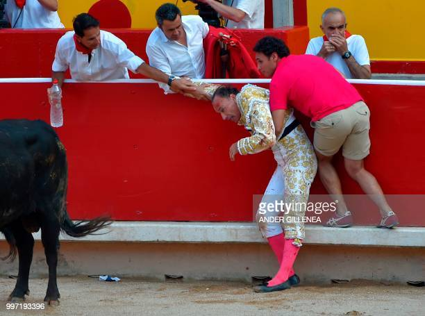 Spanish matador Pepin Liria gets help after being tossed by a Victoriano del Rio fighting bull during a bullfight of the San Fermin festival in...