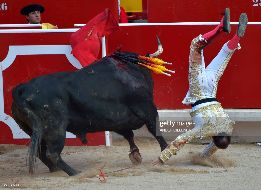 Spanish matador Pepin Liria is tossed by a Victoriano del Rio fighting bull during a bullfight of the San Fermin festival in Pamplona, northern Spain on July 12, 2018. - Each day at 8am hundreds of people race with six bulls, charging along a winding, 848.6-metre (more than half a mile) course through narrow streets to the city's bull ring, where the animals are killed in a bullfight or corrida, during this festival dating back to medieval times and also featuring religious processions, folk dancing, concerts and round-the-clock drinking.