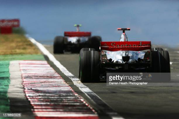 Spanish McLaren Formula One driver Fernando Alonso drives his MP4-22 car as he chases his British teammate Lewis Hamilton during 2007 Hungarian Grand...
