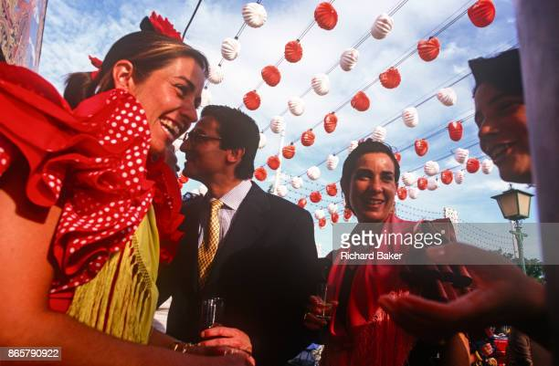 Spanish men and women party in mixed company at a private party outside a marquee called a Caseta during the annual Feria de Abril on 11th June 1999...