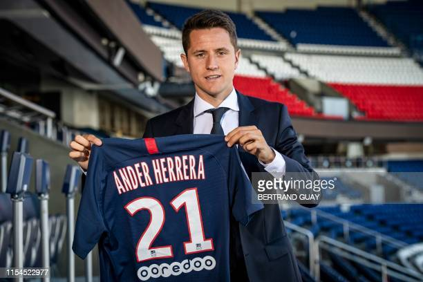 Spanish midfielder Ander Herrera poses with the PSG jersey after he signed a five-year contract with the Paris Saint-Germain football club at the...