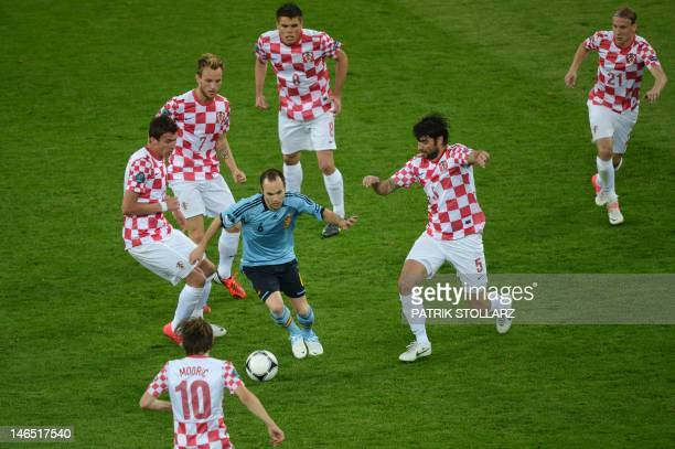 Spanish midfielder Andres Iniesta drives the ball surrounded by Croatian players during the Euro 2012 football championships match Croatia vs Spain...