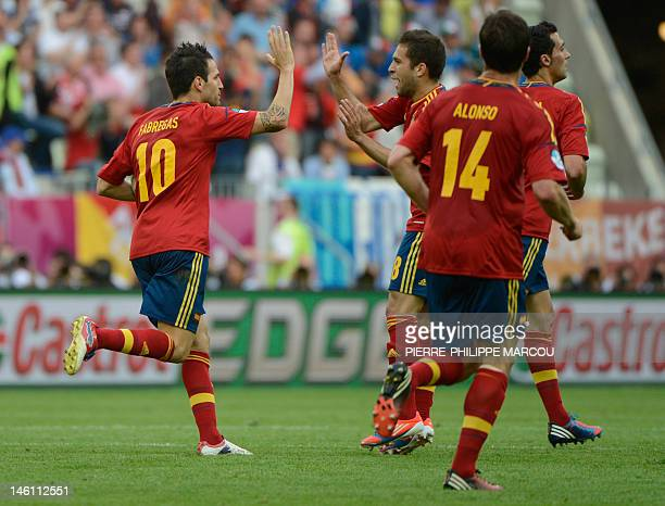 Spanish midfielder Cesc Fabregas celebrates with teammates after scoring during the Euro 2012 championships football match Spain vs Italy on June 10...