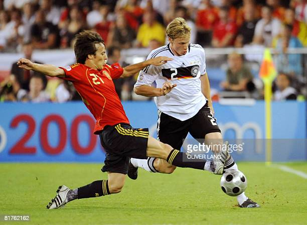 Spanish midfielder David Silva challenges German defender Marcell Jansen during the Euro 2008 championships final football match Germany vs Spain on...