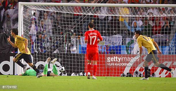 Spanish midfielder David Silva gestures after scoring a goal against Russian goalkeeper Igor Akinfeev as Spanish forward Daniel Guiza runs to join...