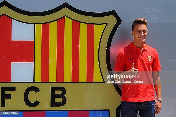 Spanish midfielder Denis Suárez poses in front of the F.C.Barcelona shield after signing for F.C.Barcelona on July 5, 2016 in Barcelona, Spain.