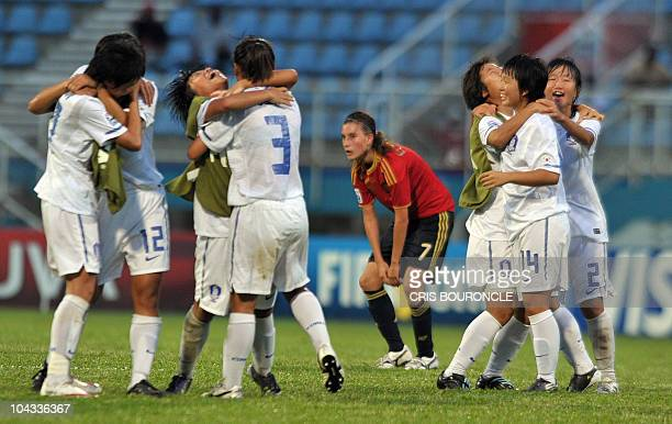 Spanish midfielder Gema Gili reacts in dejection among Korean players celebrating in the pitch their victory over Spain by 21 after the FIFA Women's...