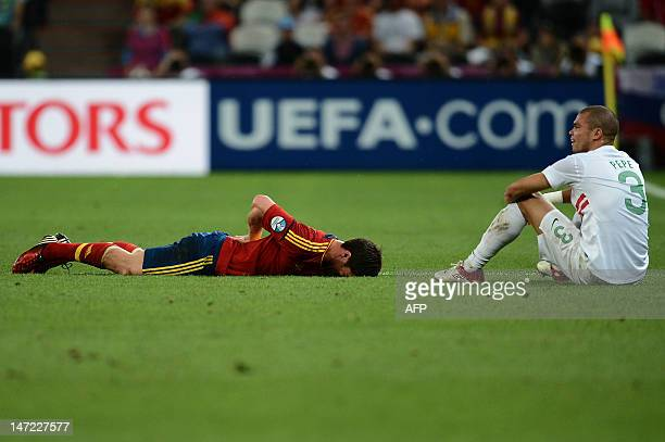 Spanish midfielder Xabi Alonso lies on the pitch next to Portuguese defender Pepe during the Euro 2012 football championships semifinal match...
