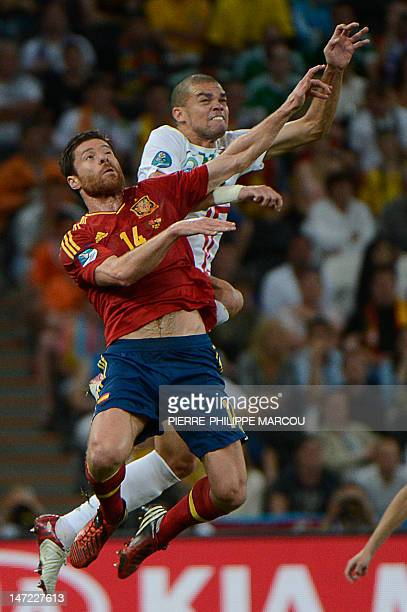 Spanish midfielder Xabi Alonso vies with Portuguese defender Pepe during the Euro 2012 football championships semifinal match Portugal vs Spain on...