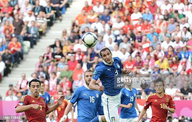 Spanish midfielder Xavi Hernandez looks at a header from Italian defender Giorgio Chiellini during the Euro 2012 championships football match Spain...