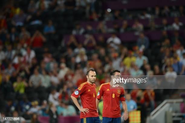 Spanish midfielders Andres Iniesta and Xavi Hernandez wait for the start of the Euro 2012 football championships semi-final match Portugal vs Spain...