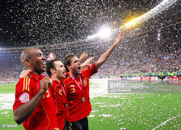 Spanish midfielders Marcos Senna and Andres Iniesta and defender Fernando Navarro celebrate with supporters after winning the Euro 2008 championships...