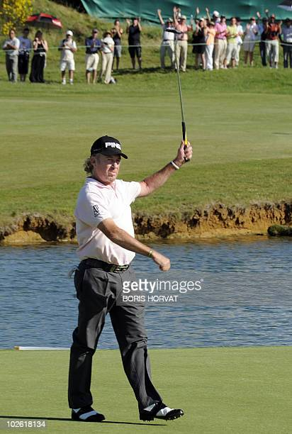 Spanish Miguel Angel Jimenez holds up his club during the French Open on July 4 2010 in St Quentin en Yvelines west of Paris at the end of a threeway...