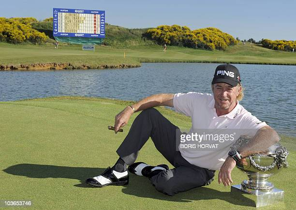 Spanish Miguel Angel Jimenez poses with the winner's trophy at the French Open on July 4 2010 in St Quentin en Yvelines west of Paris after a...