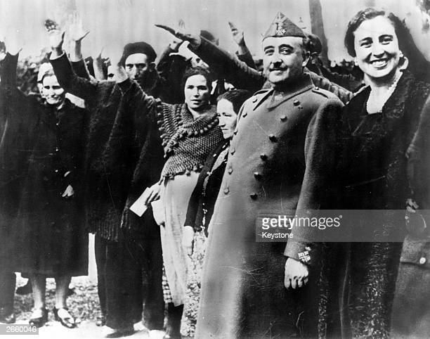 Spanish military dictator General Francisco Franco and his wife Dona Carmen Polo are saluted at a reception at Burgos to award the parents of large...