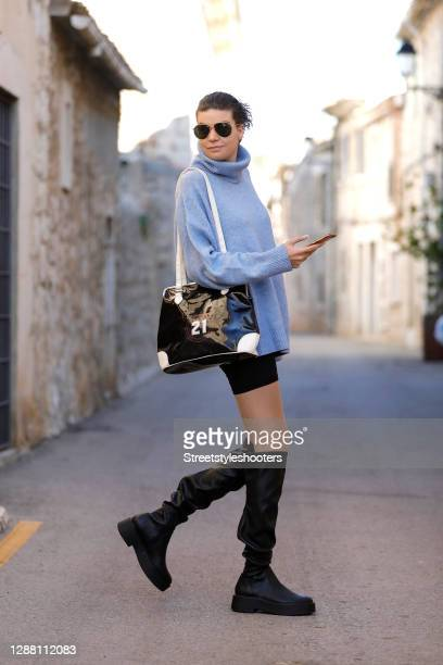 Spanish model Claire Alemany wearing a light blue knitted turtleneck pullover by Mango, black knee high boots by Mango, a black and white vintage bag...