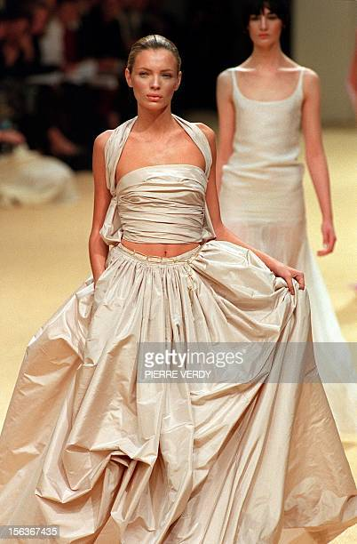 Spanish model Esther Canadas displays an ample ecru skirt with a matching wraparound halter top during the 1999 Spring/Summer haute couture show of...