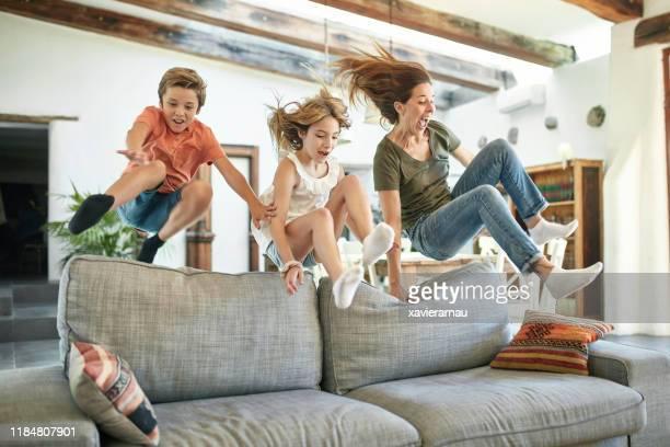 madre e bambini spagnoli che saltano sul retro del divano - saltare foto e immagini stock