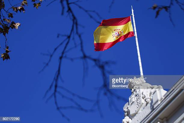 A Spanish national flag flies above the Madrid stock exchange also known as Bolsa y Mercado in Madrid Spain on Monday Dec 21 2015 Spanish bonds and...