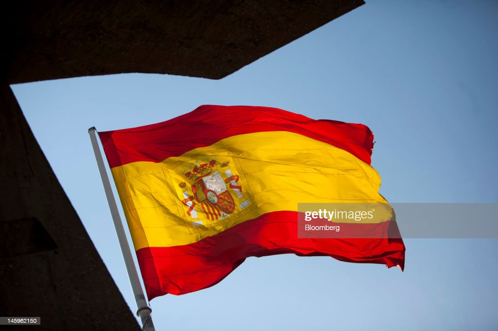 A Spanish national flag flies in Madrid, Spain, on Friday, June 8, 2012. Spain is poised to become the fourth of the 17 euro-area countries to require emergency assistance as the currency bloc's finance chiefs plan weekend talks on a potential aid request to shore up the nation's lenders. Photographer: Angel Navarrete/Bloomberg via Getty Images