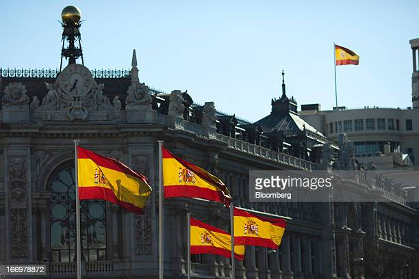 Spanish national flags fly outside the headquarters of the Spanish central bank in Madrid Spain on Thursday April 18 2013 A Spanish economic slump...