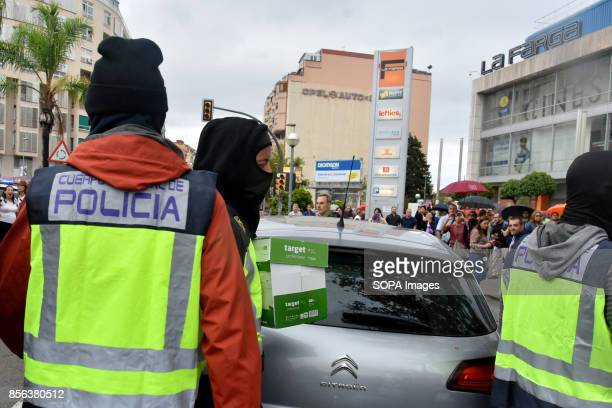 Spanish National Police are seen carrying boxes with the voting material for the referendum National Police entered by force in the High School of...
