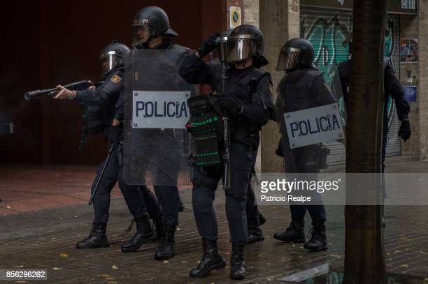Spanish National Police fire rubber bullets after storming into polling station to confiscate ballot boxes during the referendum on October 1 2017 in...