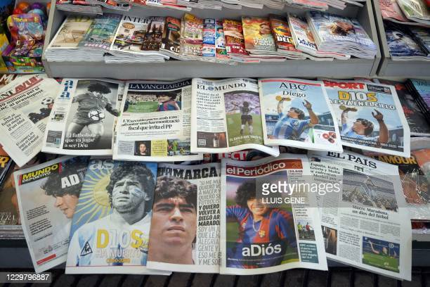 Spanish newspapers featuring front-page news on the death of Argentinian player Diego Maradona are displayed at a newsstand in Barcelona on November...