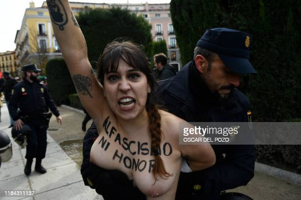 Spanish officer restrains a member of the feminist movement Femen as she protests against a far right demonstration marking the anniversary of the...