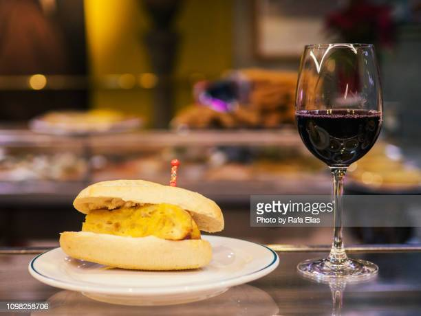 spanish omelette sandwich and glass of red wine - tortilla de patata fotografías e imágenes de stock