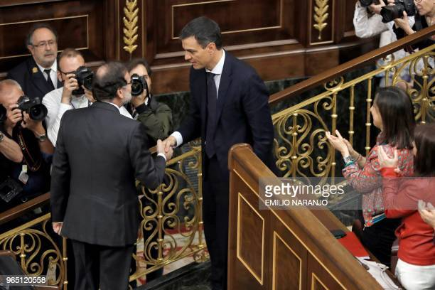 TOPSHOT Spanish outgoing Prime Minister Mariano Rajoy shakes hands with Spain's new Prime Minister Pedro Sanchez after a vote on a noconfidence...
