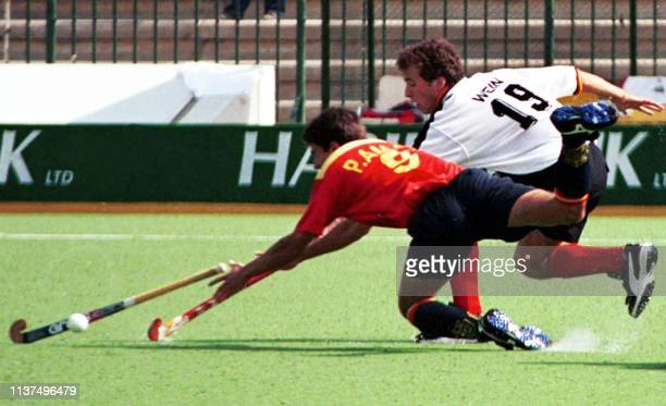 Spanish Pablo Amat and German player Christian Wein struggle to get hold of the ball in the first half of the match in 20th field Hockey Champions...