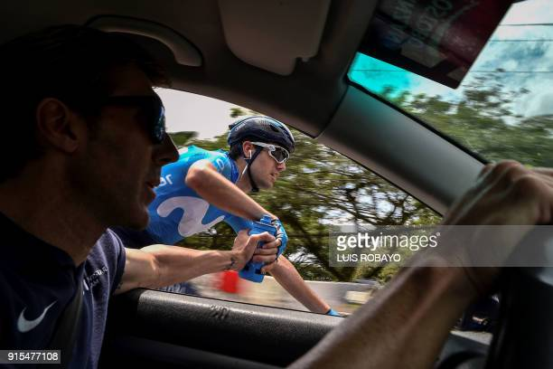 Spanish Pablo Lastras Sports Director of Movistar Team hands a bottle of water to Spanish cyclist Antonio Pedrero during the second stage of the...