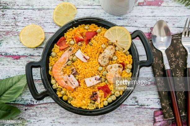 spanish paella on a wooden table - spanische kultur stock-fotos und bilder