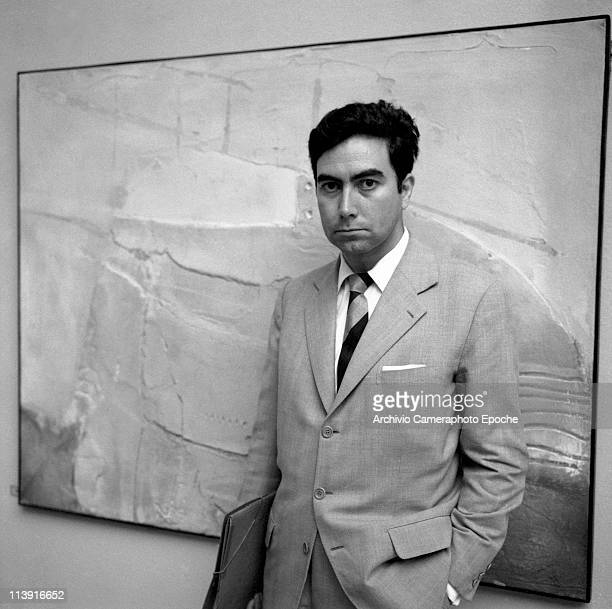 Spanish painter Antonio Tapies wearing a suit and holding a folder presents his paintings at the Art Biennale in Venice 1958