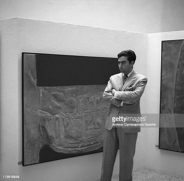 Spanish painter Antonio Tapies wearing a suit standing next to his paintings displayed at the Art Biennale in Venice 1958