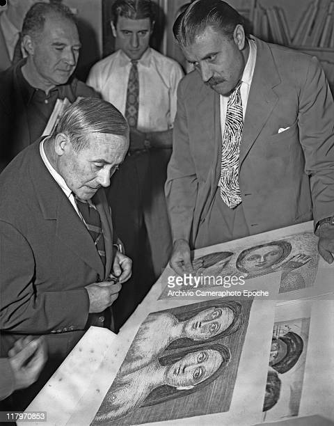 Spanish painter Joan Miro wearing a suit and a striped tie portrayed while looking at Campigli drawings the art promoter Carlo Cardazzo next to him...