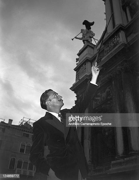 Spanish painter Salvador Dalì wearing a velvet doublebreasted blazer and a tie portrayed while showing a church detail with his walking stick Venice...
