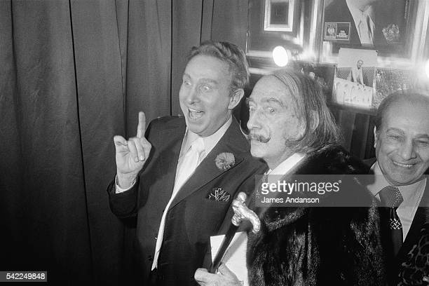 Spanish painter Salvador Dali with singer Tino Rossi congratulating French singer composer and actor Charles Trénet after his concert at the Olympia