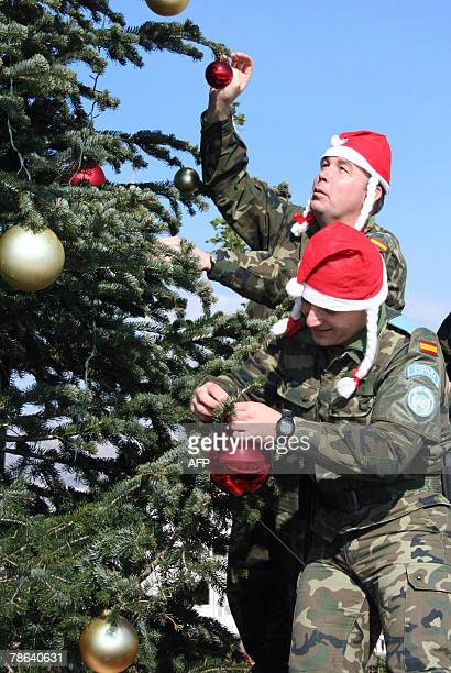 Spanish peacekeeping soldiers with the United Nations Interim Force in Lebanon wearing Santa's hat decorate a Christmas tree at their base in the...