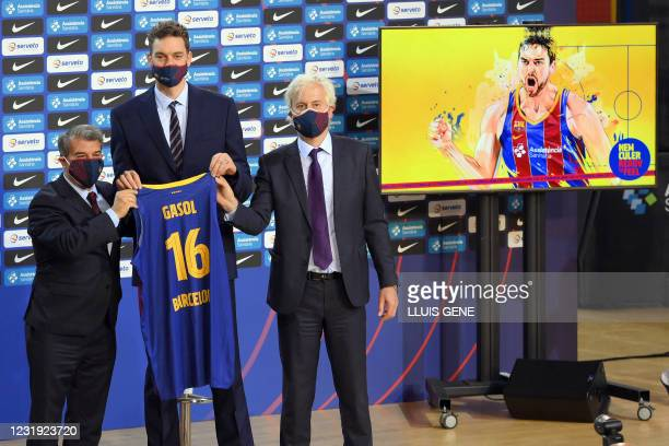 Spanish pivot Pau Gasol holds his new vest with FC Barcelona president Joan Laporta and the club's responsible for the basketball section Josep...