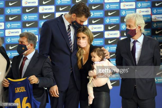 Spanish pivot Pau Gasol kisses his wife Catherine McDonnell who holds their daughter Elisabet Gianna flanked by FC Barcelona president Joan Laporta...