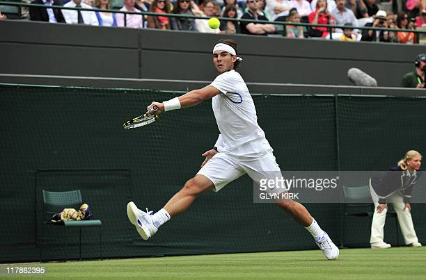 Spanish player Rafael Nadal returns the ball to Luxembourg player Gilles Muller during the men's single at the Wimbledon Tennis Championships at the...