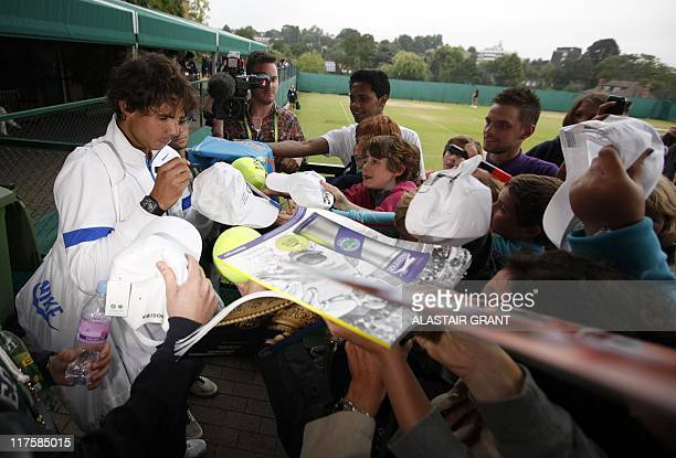 Spanish player Rafael Nadal signs autographs after a training at the Wimbledon Tennis Championships at the All England Tennis Club in southwest...