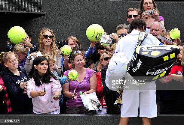 Spanish player Rafael Nadal signs autographs after beating Luxembourg player Gilles Muller during the men's single at the Wimbledon Tennis...