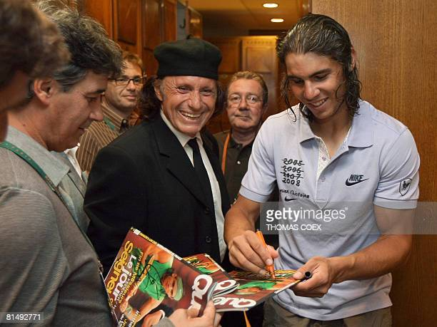 Spanish player Rafael Nadal signs autographs prior to a photocall in the locker room of the Philippe Chatrier stadium after winning against Swiss...