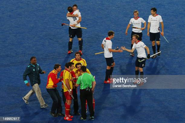 Spanish players argue with match referee John Wright of South Africa during the Men's Hockey match between Great Britain and Spain on Day 11 of the...
