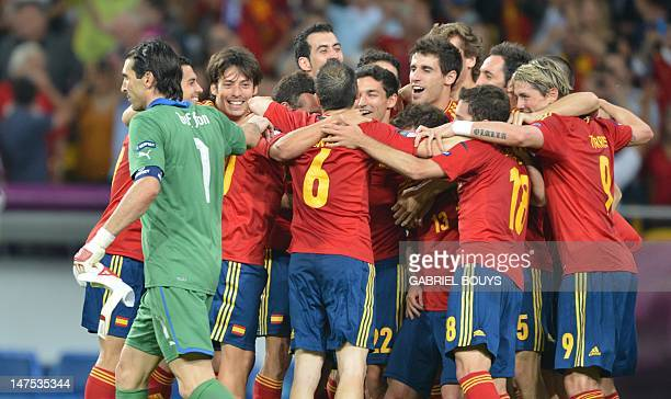 Spanish players celebrate as Italian goalkeeper Gianluigi Buffon look dejected at the end of the Euro 2012 football championships final match Spain...