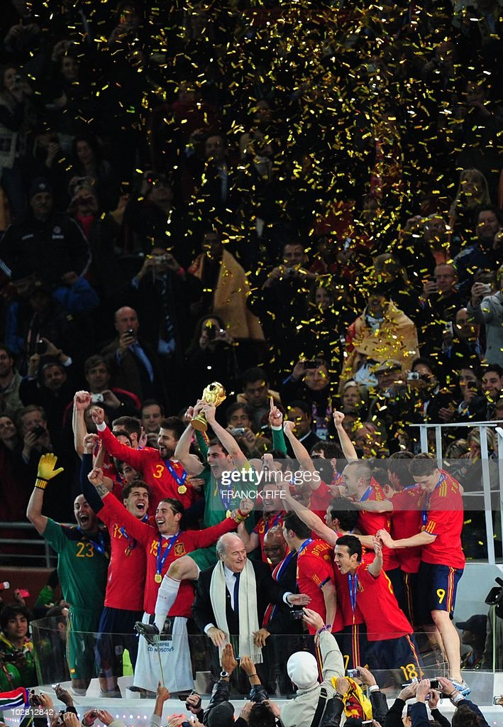 Spanish players celebrate with the trophy during the award ceremony following the 2010 World Cup final football match between the Netherlands and Spain on July 11, 2010 at Soccer City stadium in Soweto, suburban Johannesburg. NO