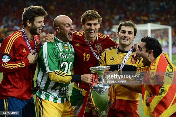 Spanish players Gerard Pique, Pepe Reina, Fernando Llorente, Iker Casillas and Xavi Hernandez pose with the trophy after winning the Euro 2012...
